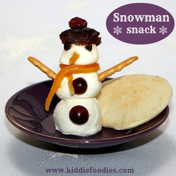 Snowman snack with mozzarella balls and dried fruits